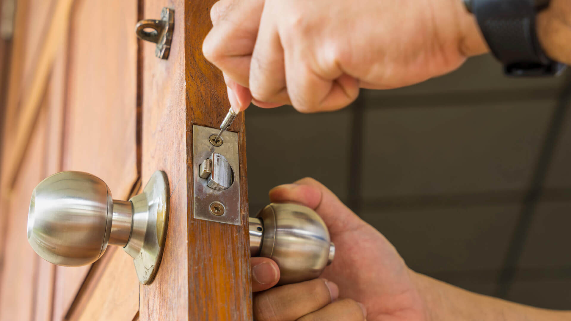 Locksmith making a repair to a residential lock in Tampa, FL.
